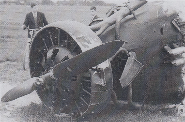 Two English School pupils looking at a crashed German plane in May 1940 in a field near The Hague